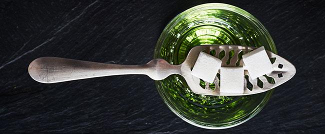 Vidrio de ajenjo con cubos de azúcar